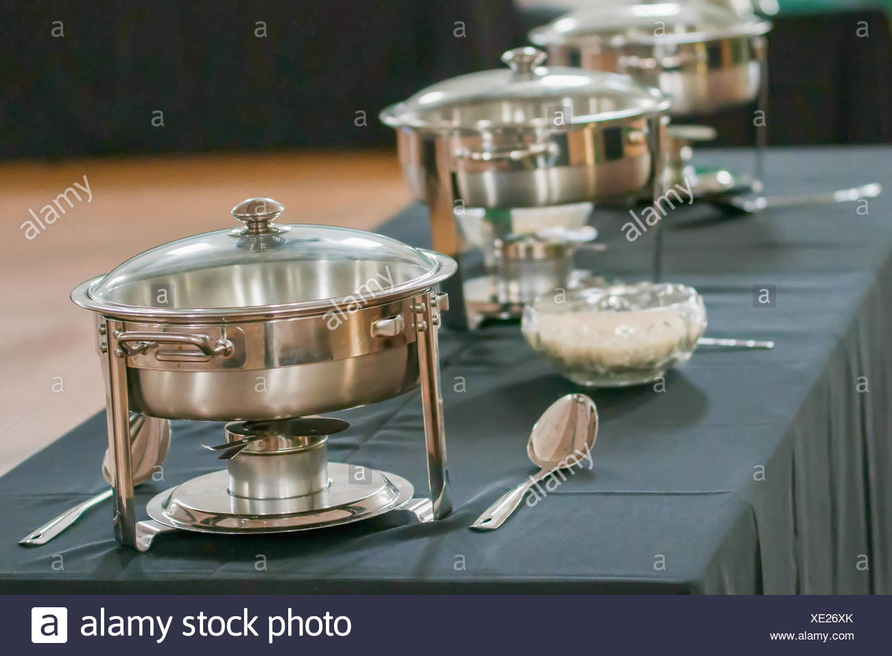 banquet table with chafing dish heaters - Stock Image