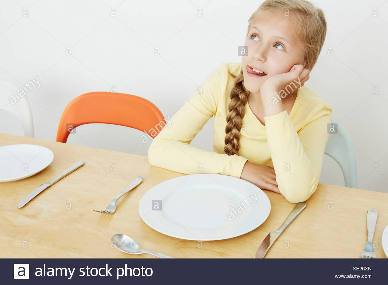 Girl sitting at table with empty plate, looking up - Stock Image