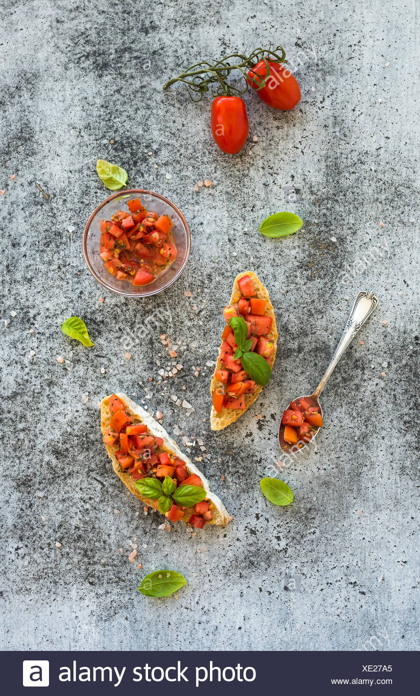Tomato and basil bruschetta sandwich over grunge gray background, top view - Stock Image