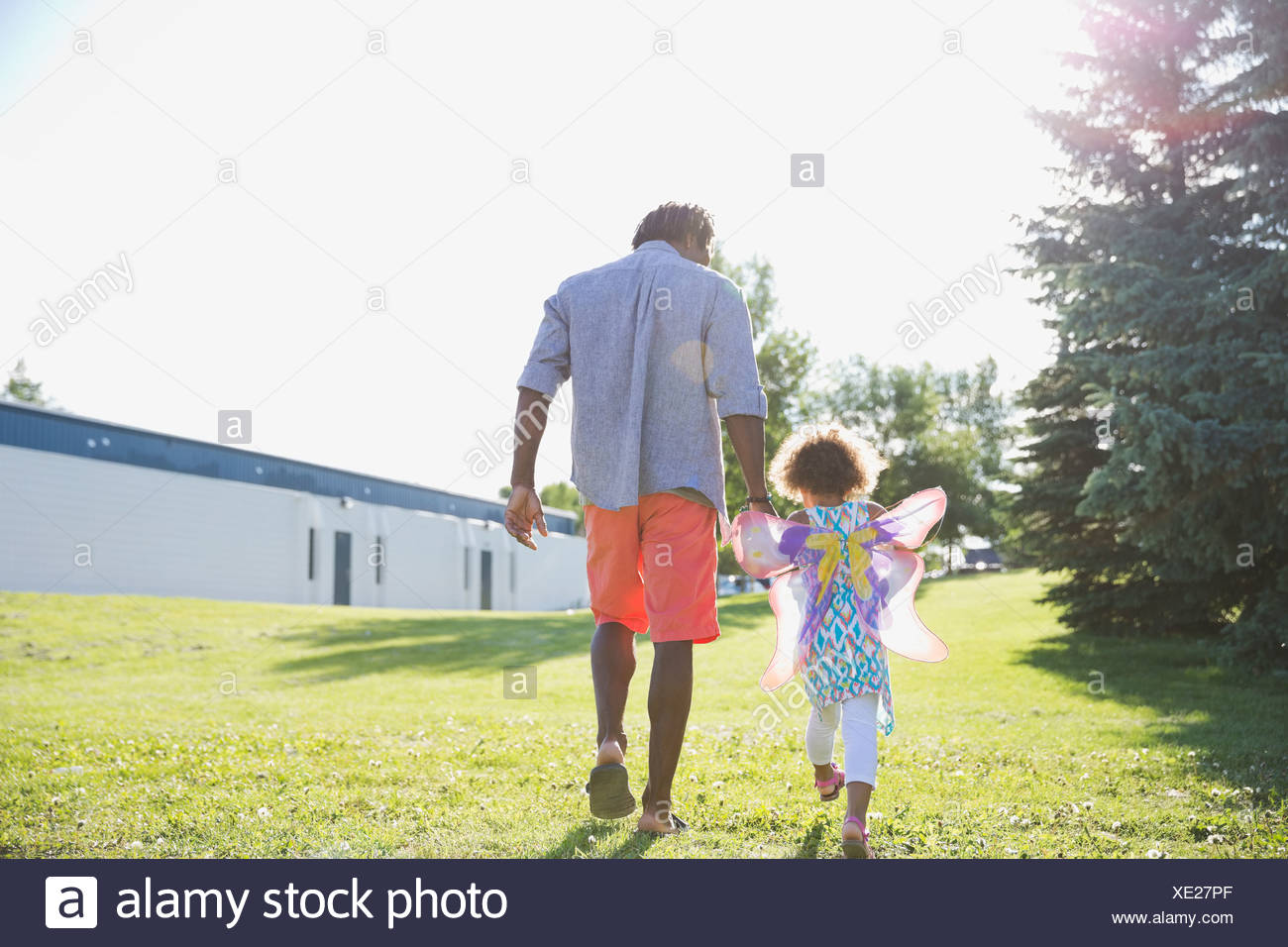 Rear view of father and daughter walking at park - Stock Image