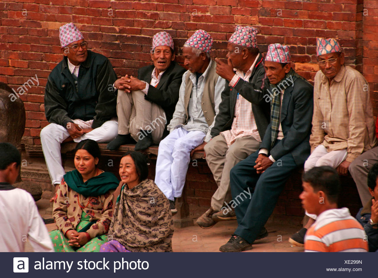 Six elderly gentlemen wearing typical Nepalese head coverings called 'topi' sitting on a bench chatting, Patan in the Kathmandu - Stock Image