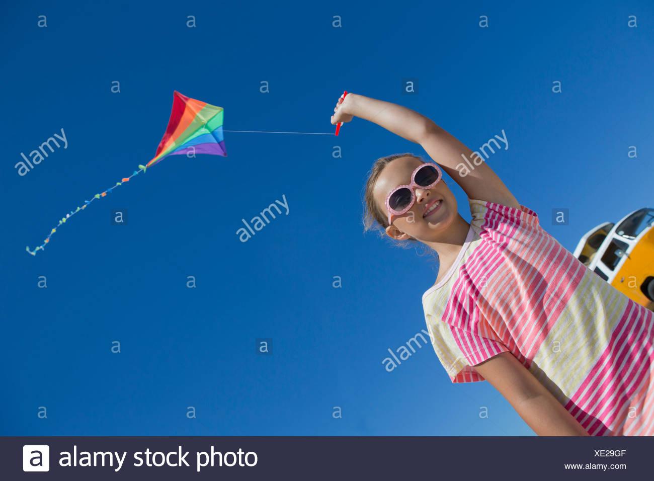 Girl flying kite against blue sky - Stock Image