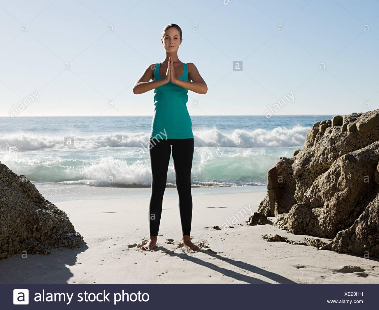 Young woman doing yoga on beach Stock Photo