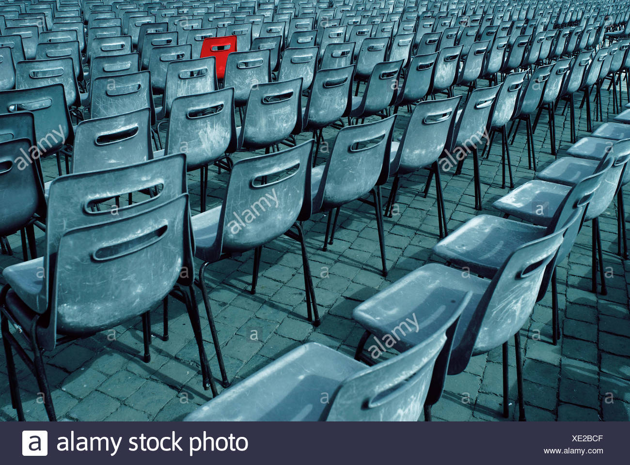 Rows of grey plastic chairs with one red chair - Stock Image