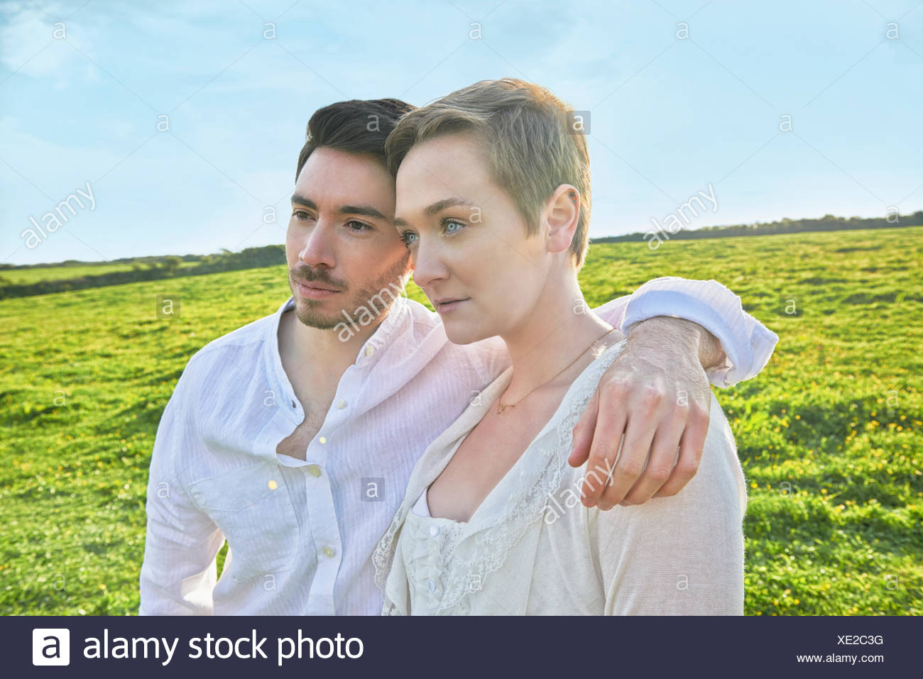 Young couple gazing in field - Stock Image