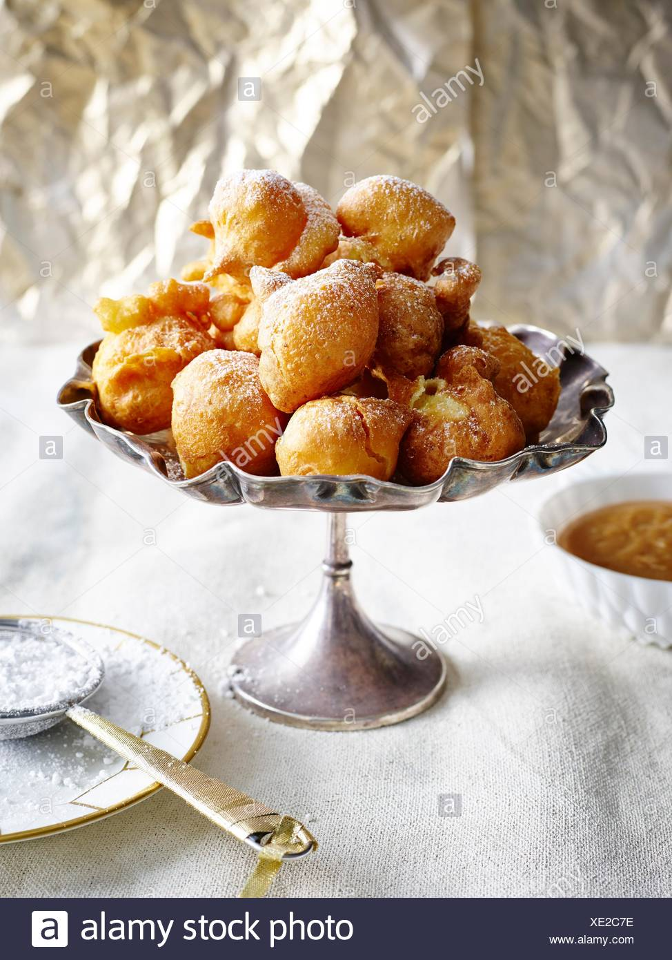 Bunuelos piled into silver serving dish dusted with icing sugar - Stock Image