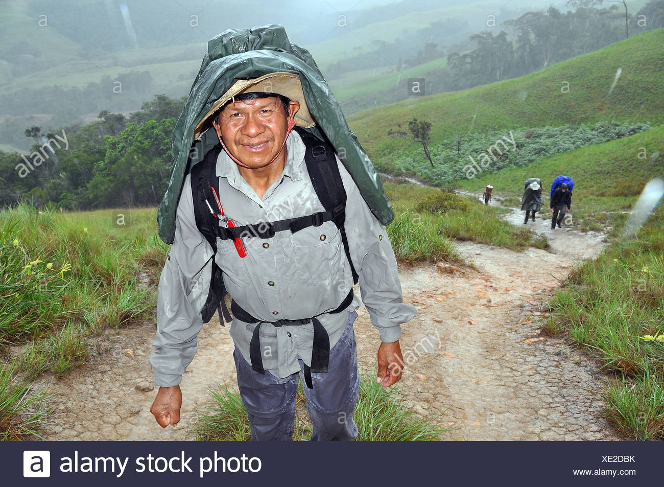 Mountaineer during a strenuous hike in the rain, Mount Roraima, table mountain, border triangle of Brazil, Venezuela and Guyana - Stock Image
