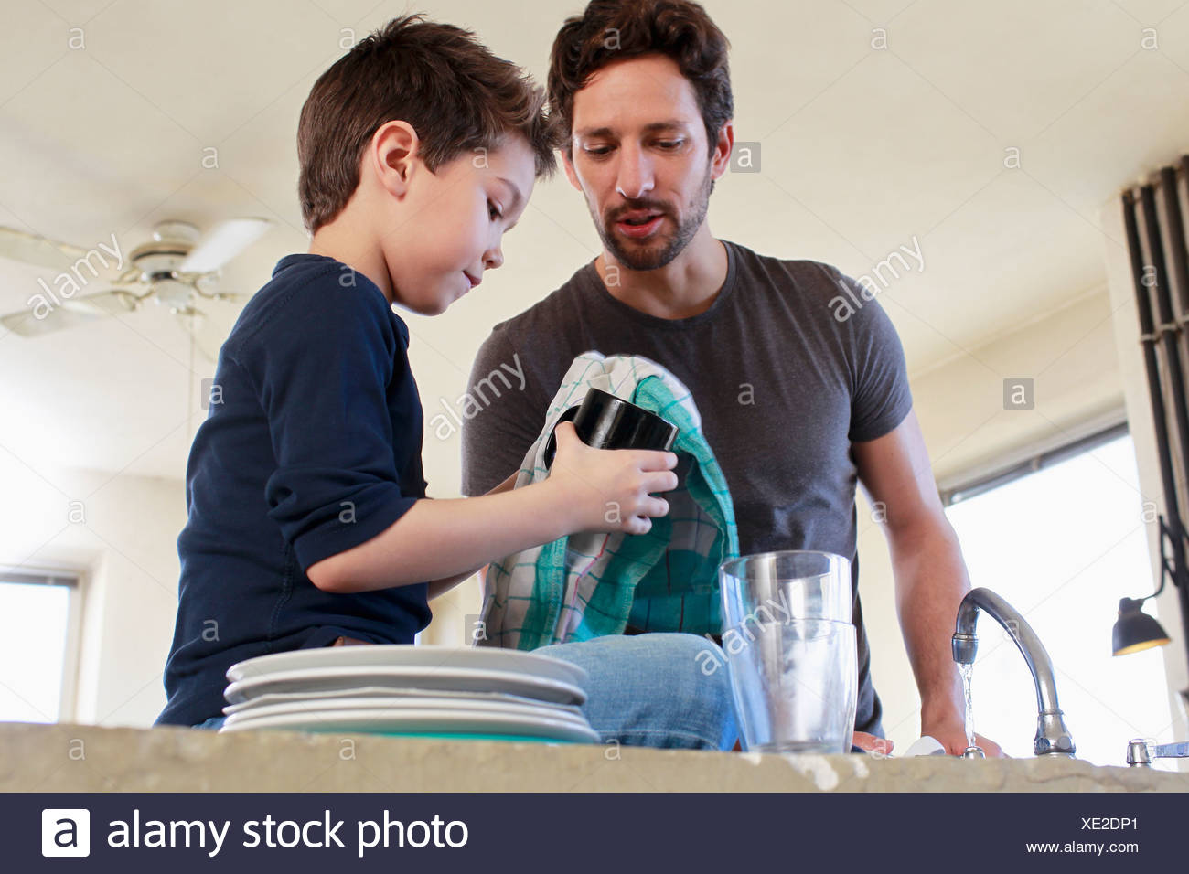 Father and son doing washing up chores - Stock Image