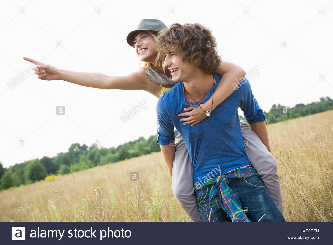 Woman showing something while enjoying piggyback ride on man in field - Stock Image