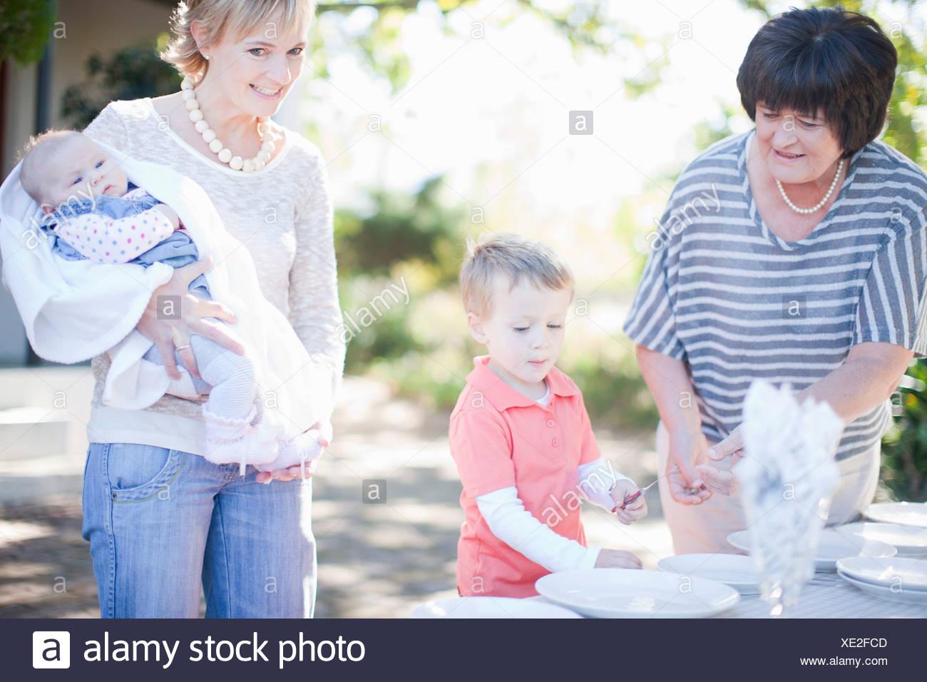Family setting dinner table outdoors - Stock Image