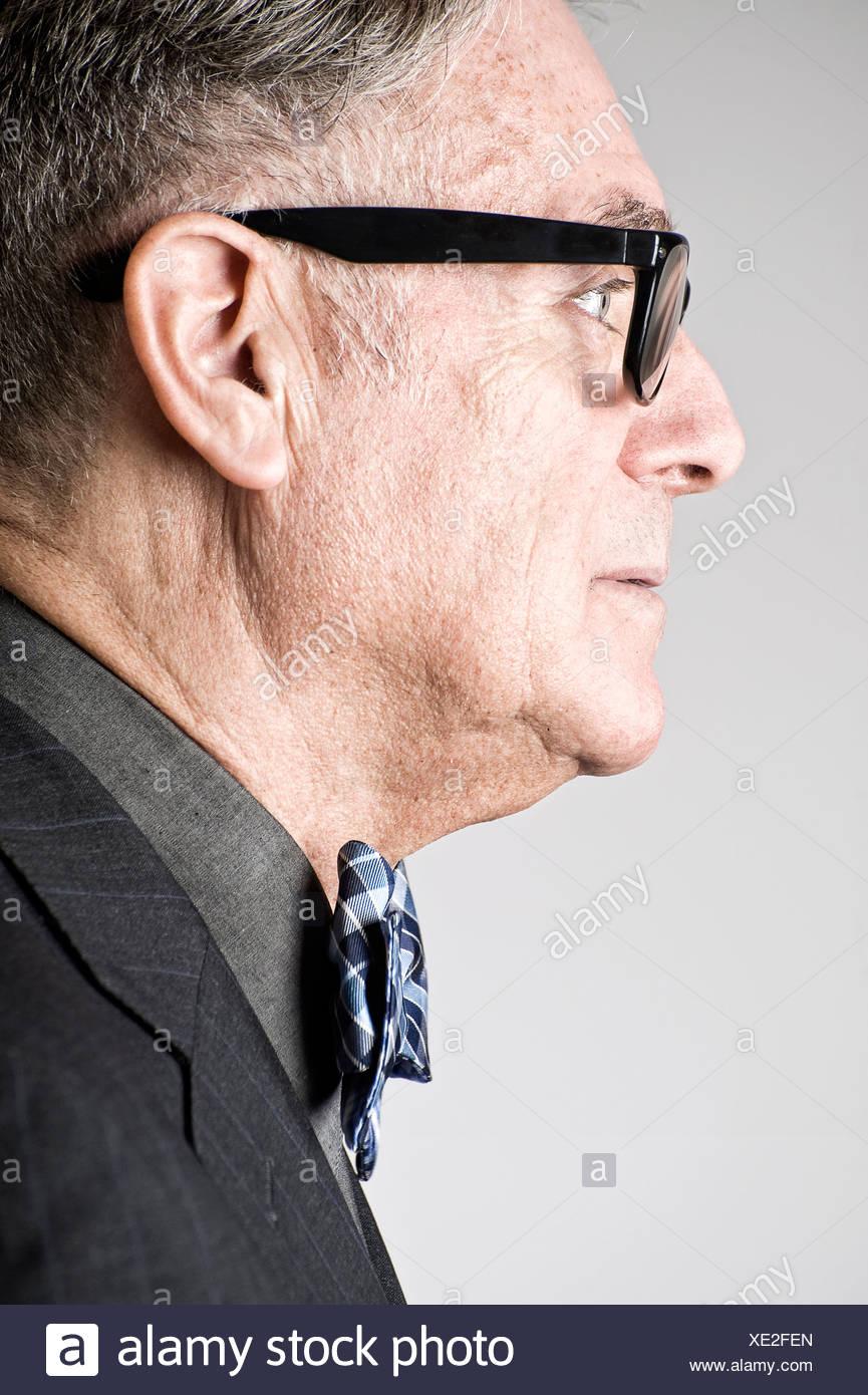 Portrait of senior man wearing bowtie, side view - Stock Image
