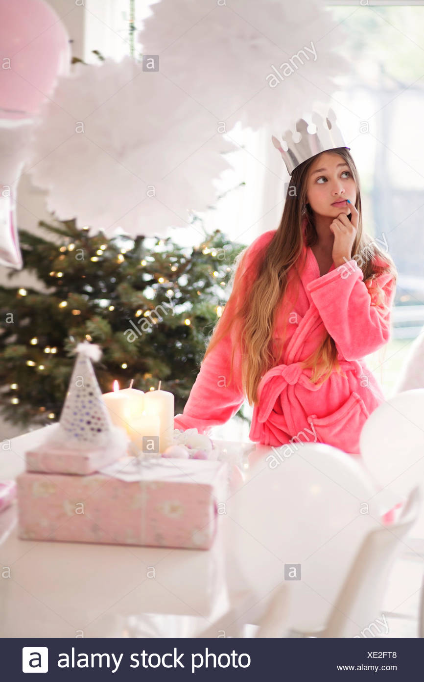 Girl (14-15) wearing paper crown and pink bathrobe standing by presents - Stock Image