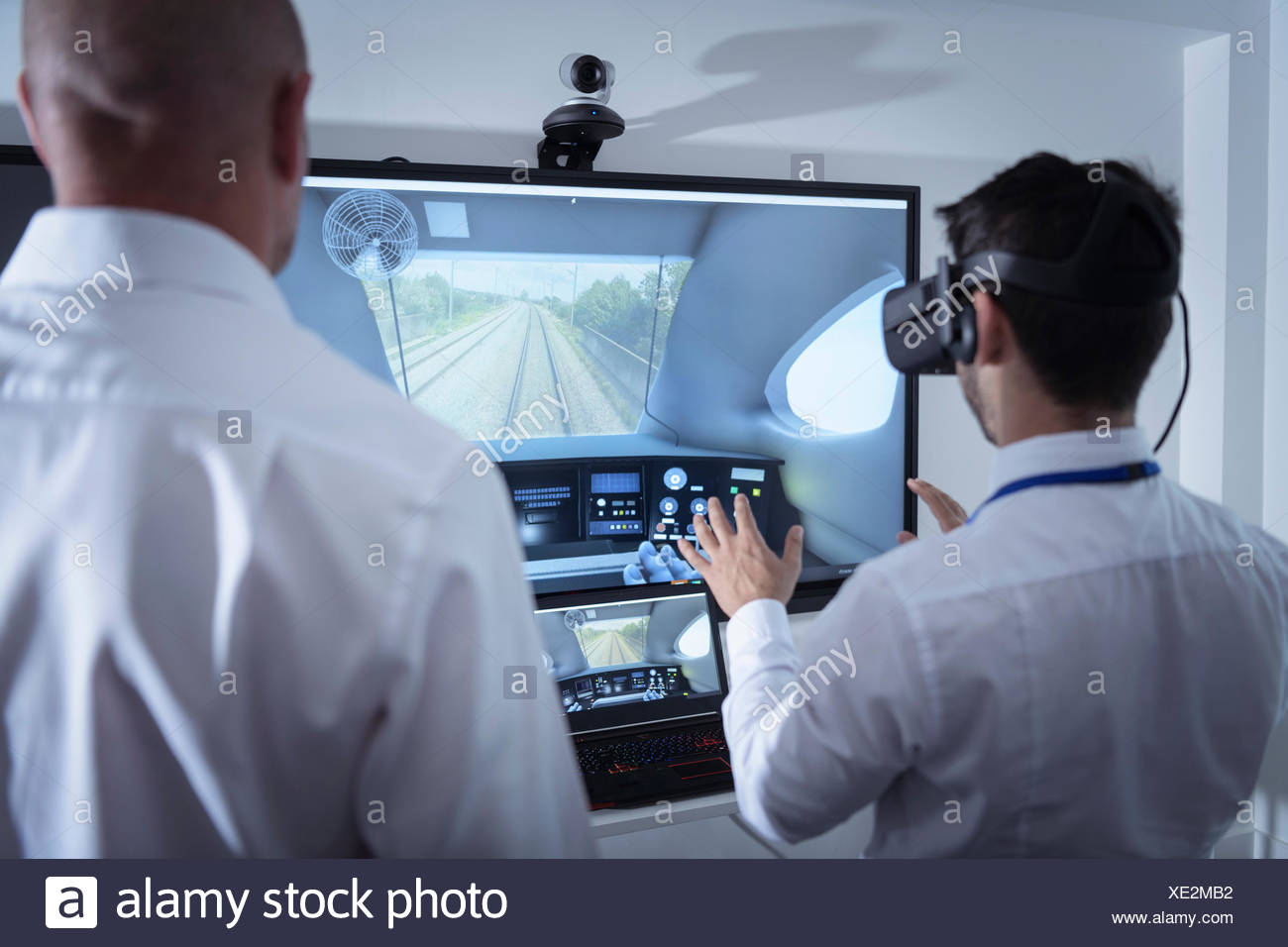 Instructor and apprentice using Virtual Reality system in railway engineering facility - Stock Image