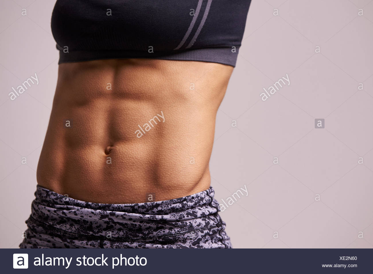 Mid-section crop shot of muscular young woman's abs - Stock Image