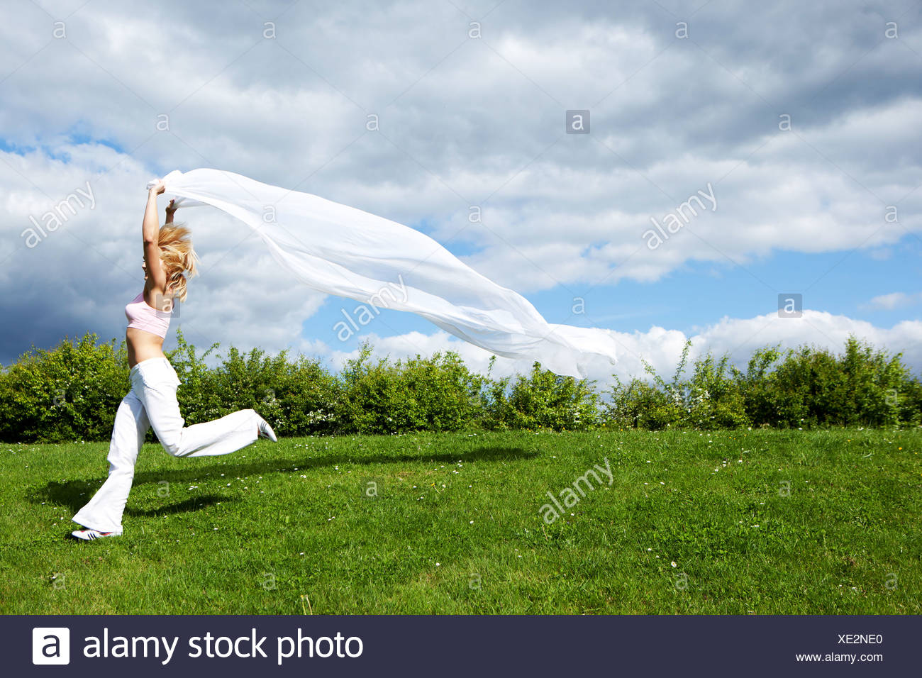 shapely blonde running with the piece of silk - Stock Image