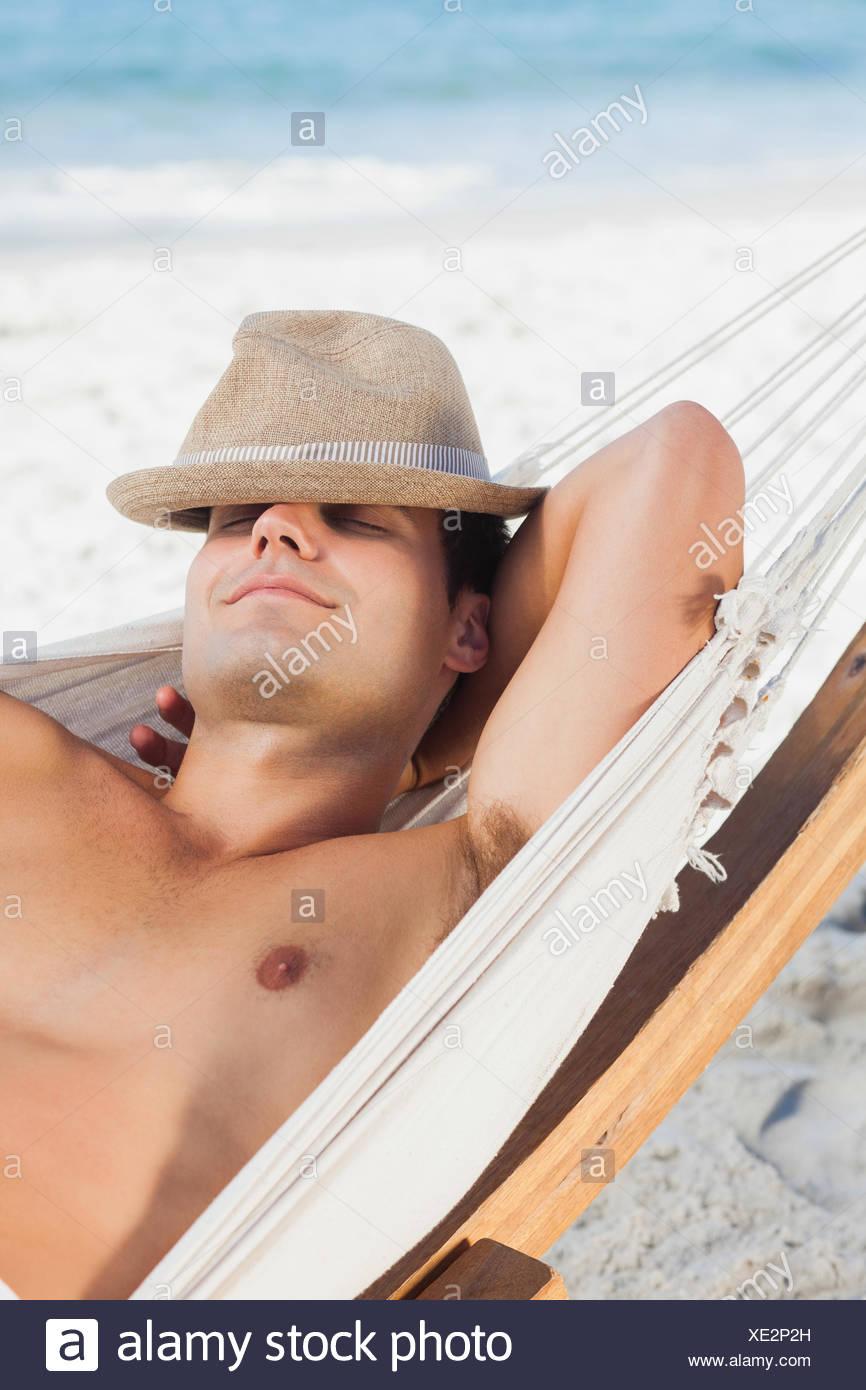 Man wearing straw hat lying in hammock Stock Photo