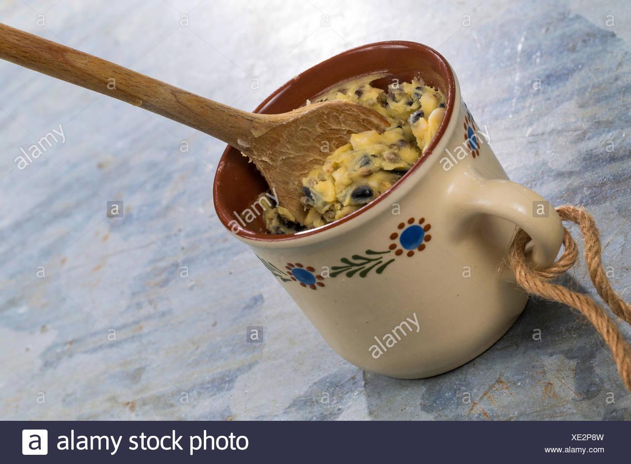 selbstgemachtes Vogelfutter wird in eine Tasse zum Aufhaengen gefuellt   self made birdseeds are filled in a cup   BLWS419327.jp Stock Photo