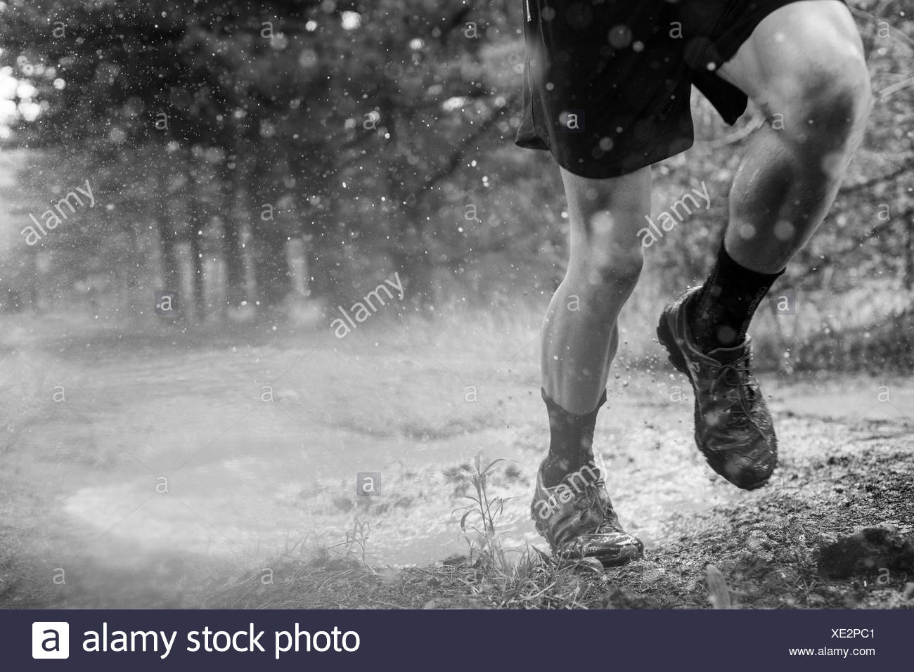 Low section of male runner splashing though puddle in Rancho Santa Elena, Hidalgo, Mexico - Stock Image