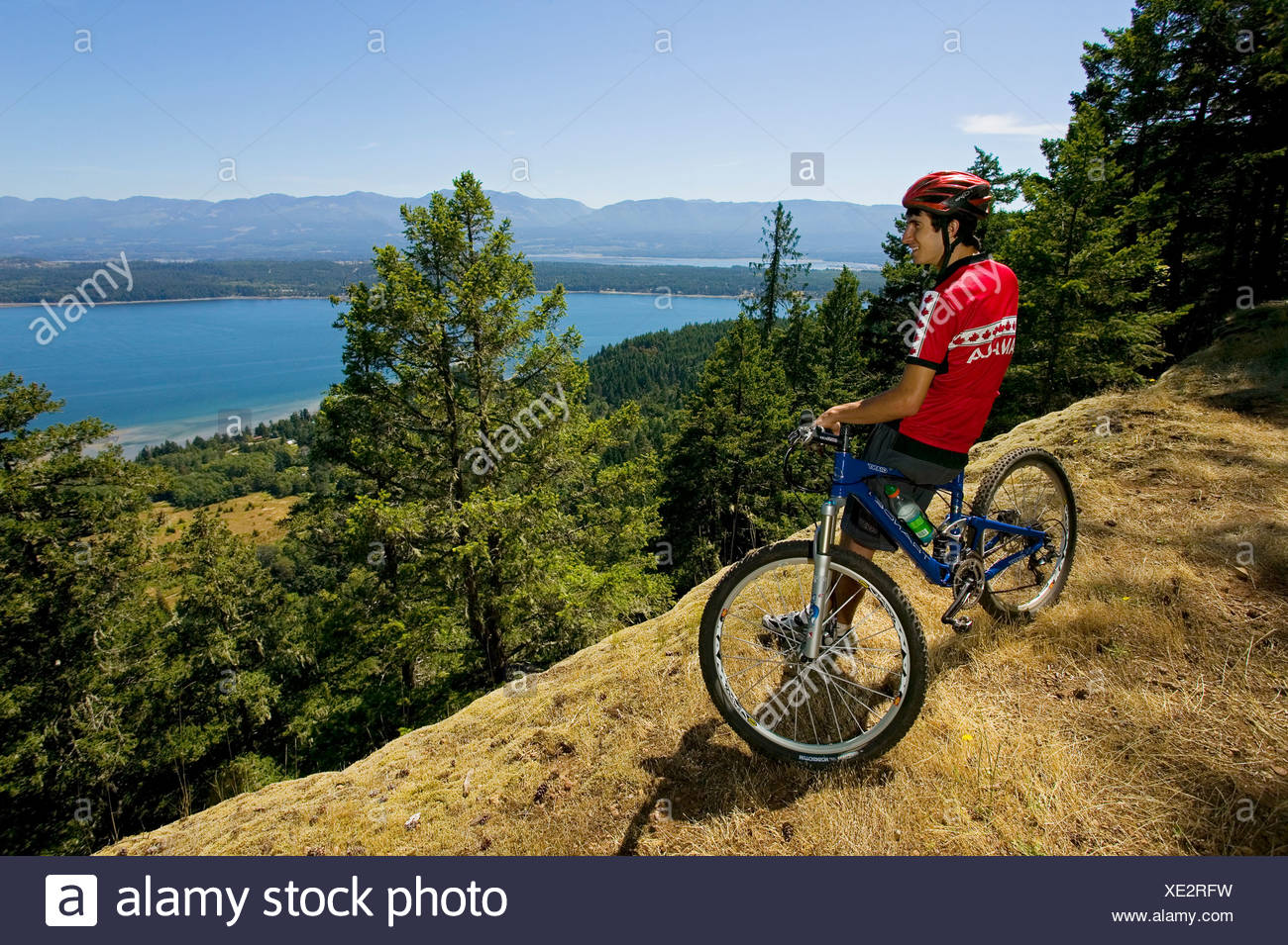 Dylan Holliday on top of Mount Geoffrey on Hornby Island overlooking Baynes sound back towards Vancouver Island.  British Columb - Stock Image