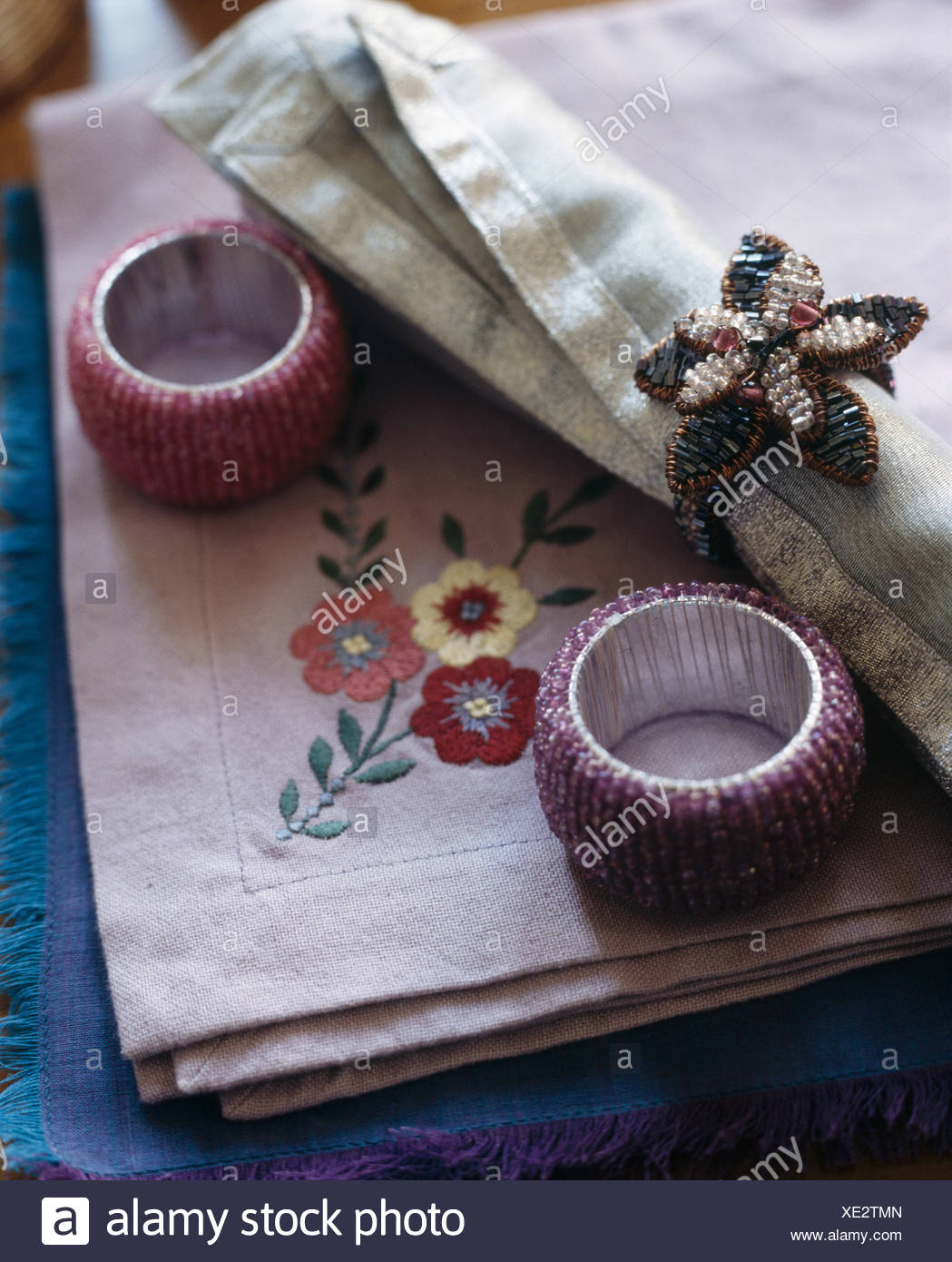 Close-up of embroidered linen table napkins with beaded napkin rings - Stock Image