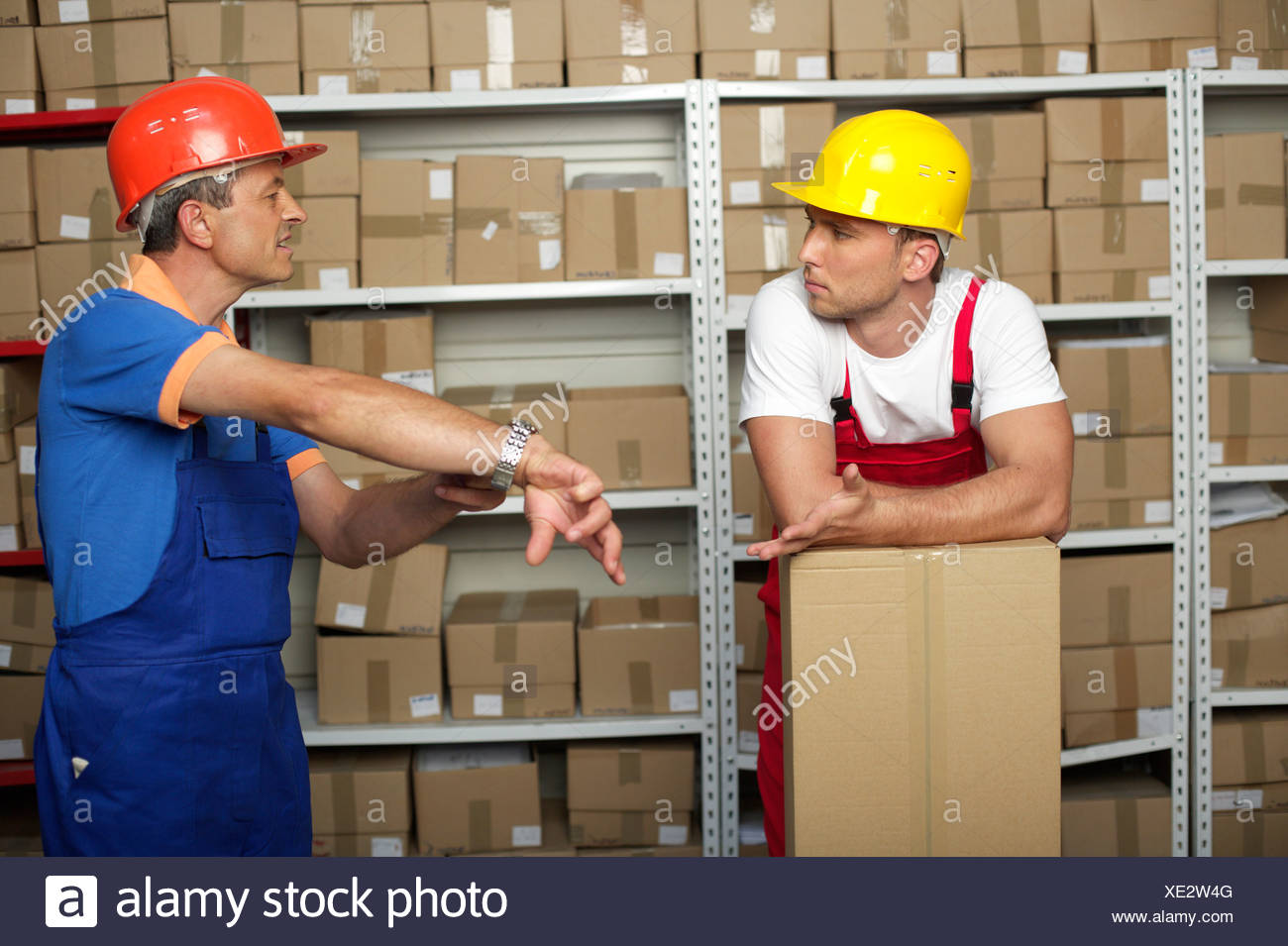 Two men in front of a shelf - Stock Image