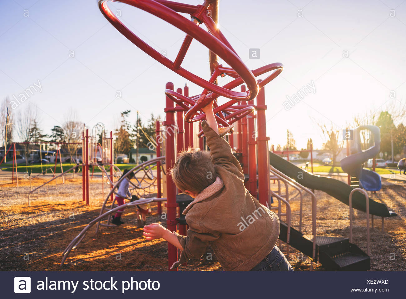 Rear view of boy swinging on monkey bars in playground - Stock Image