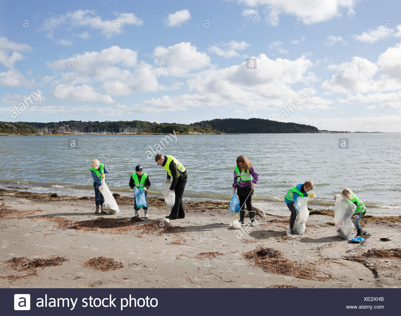 Man and children cleaning beach - Stock Image