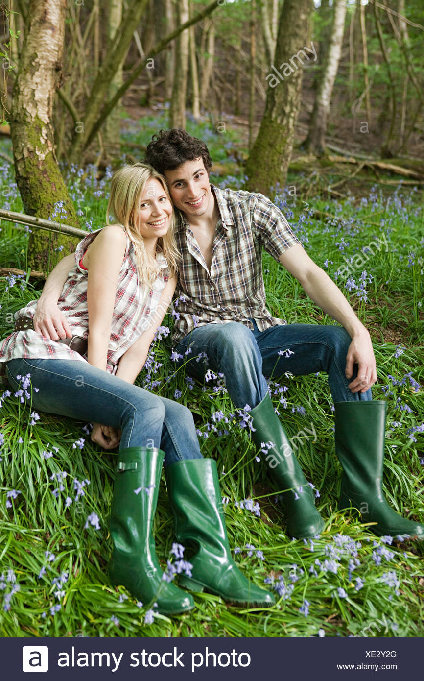 Young couple sitting amongst bluebells - Stock Image