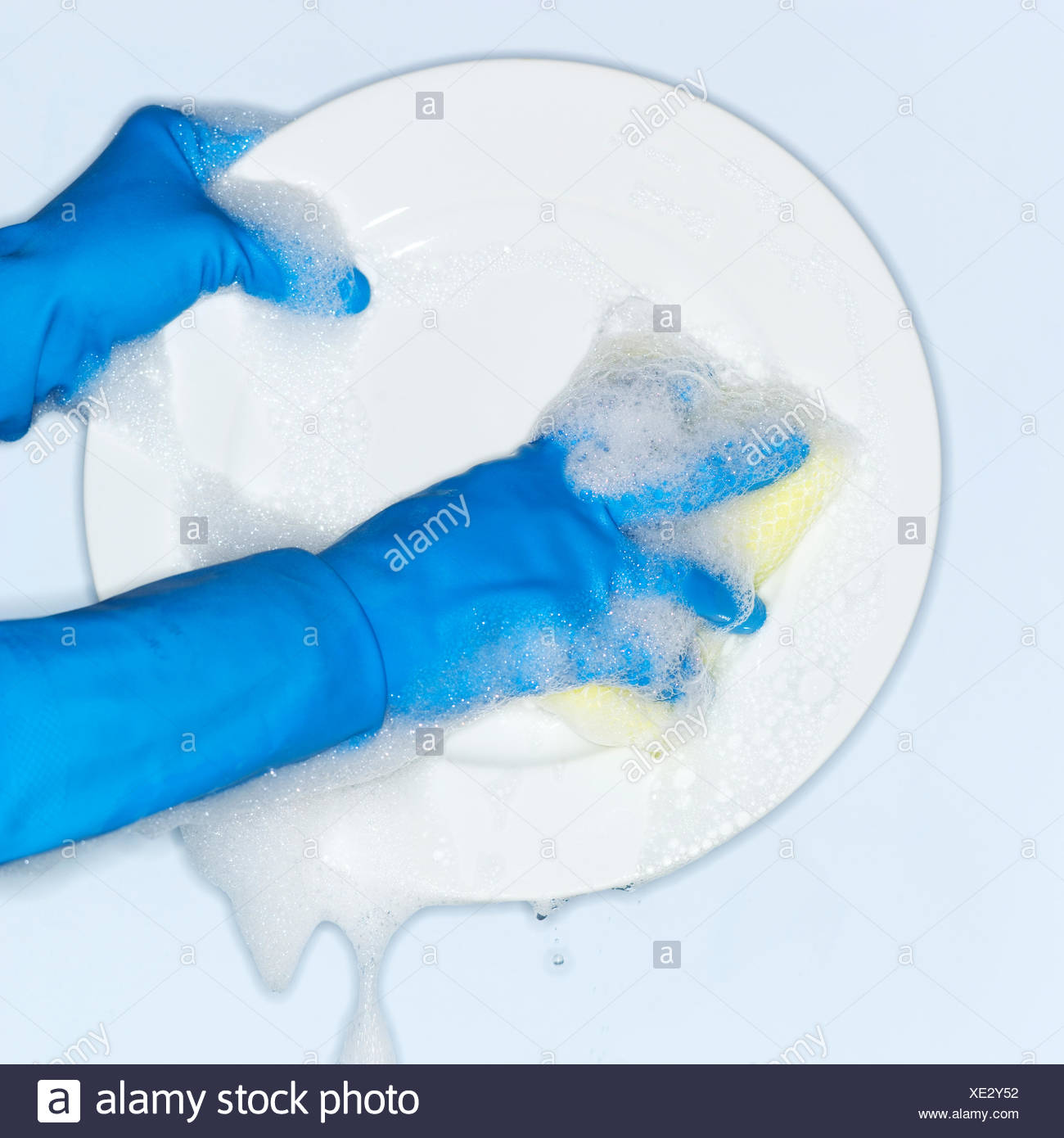 Hands in blue gloves washing plate - Stock Image