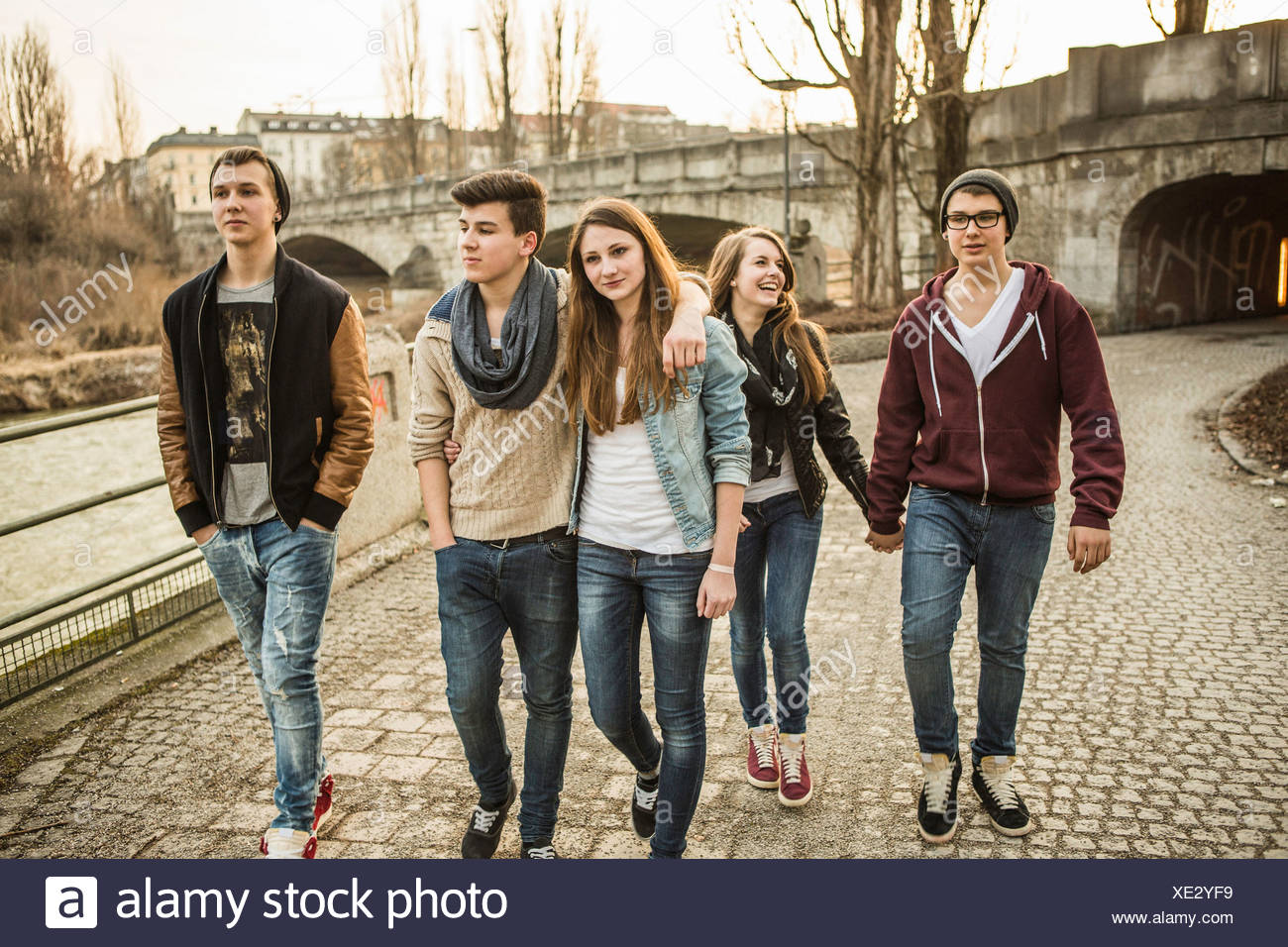 Five teenagers walking together beside river - Stock Image