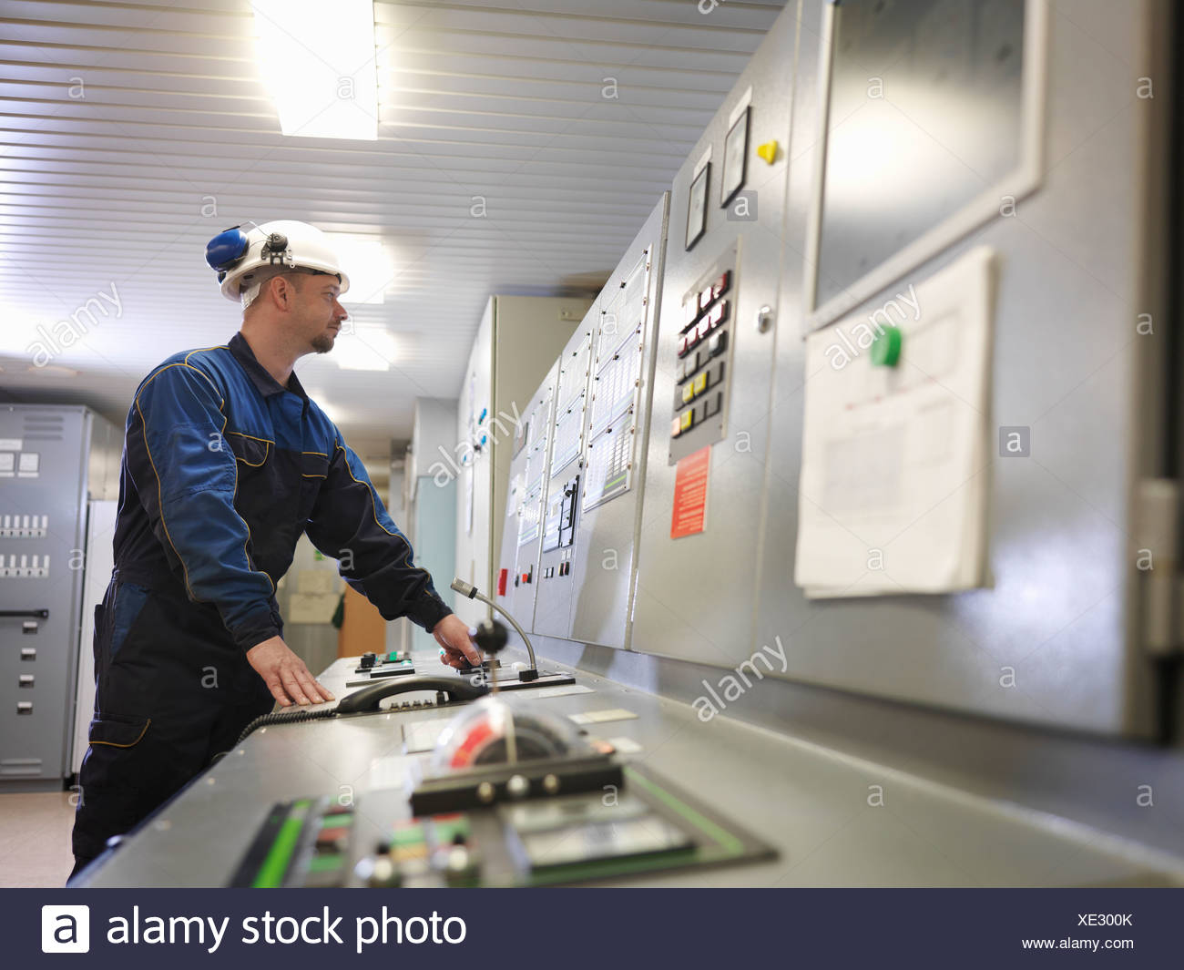 Engineer in Control Room of Ship - Stock Image