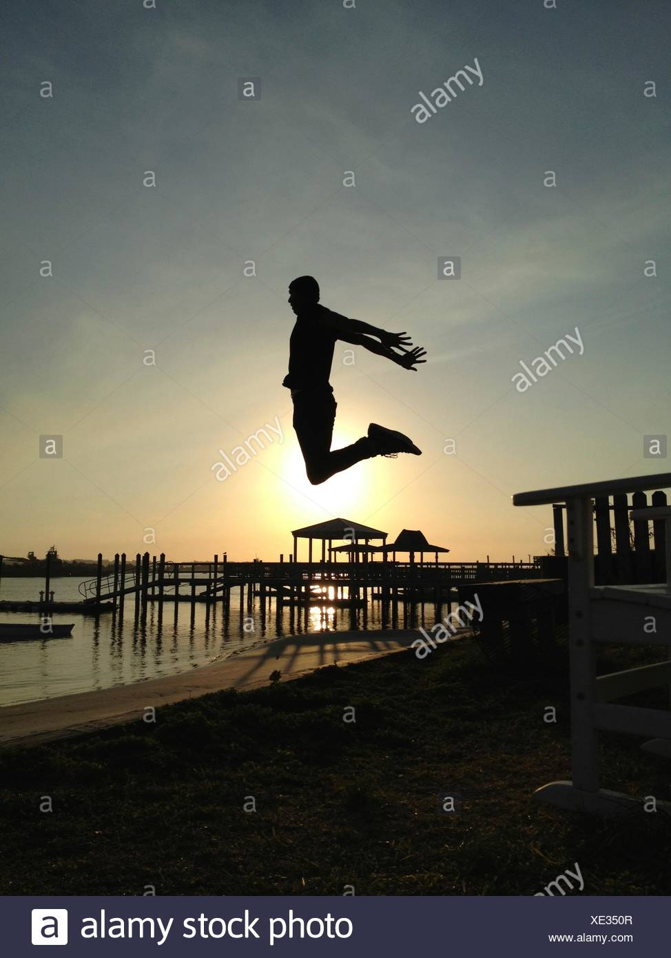 Man jumping high into sunset on beach - Stock Image