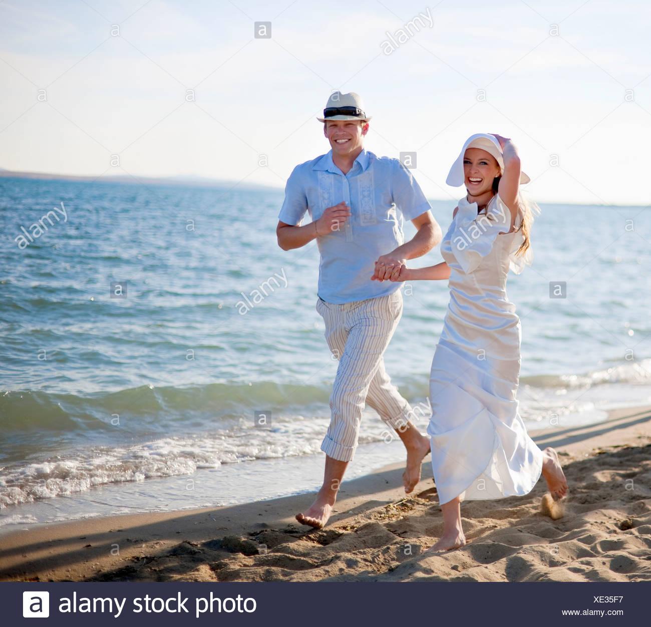 Newlywed couple running on beach Stock Photo