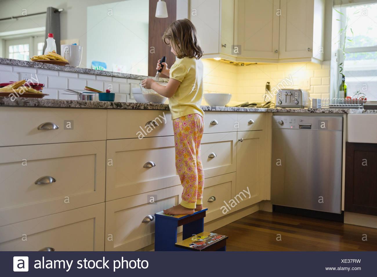 Little girl mixing waffle batter Stock Photo