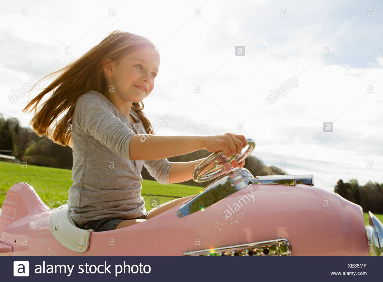 Girl driving toy airplane in field Stock Photo