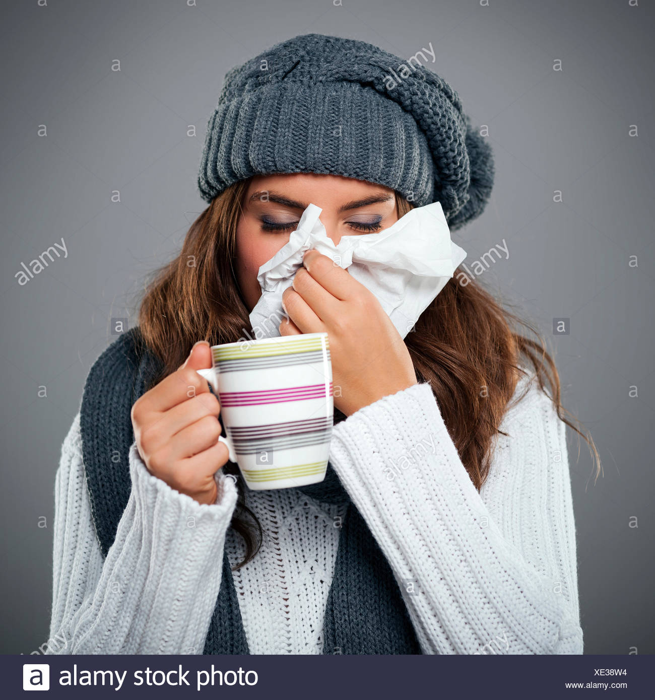 Young woman having flu and blowing her nose at handkerchief Debica, Poland - Stock Image