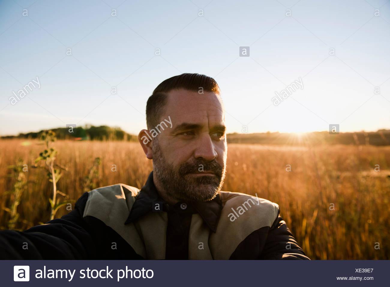 Self portrait of farmer in wheat field at sunset, Plattsburg, Missouri, USA - Stock Image