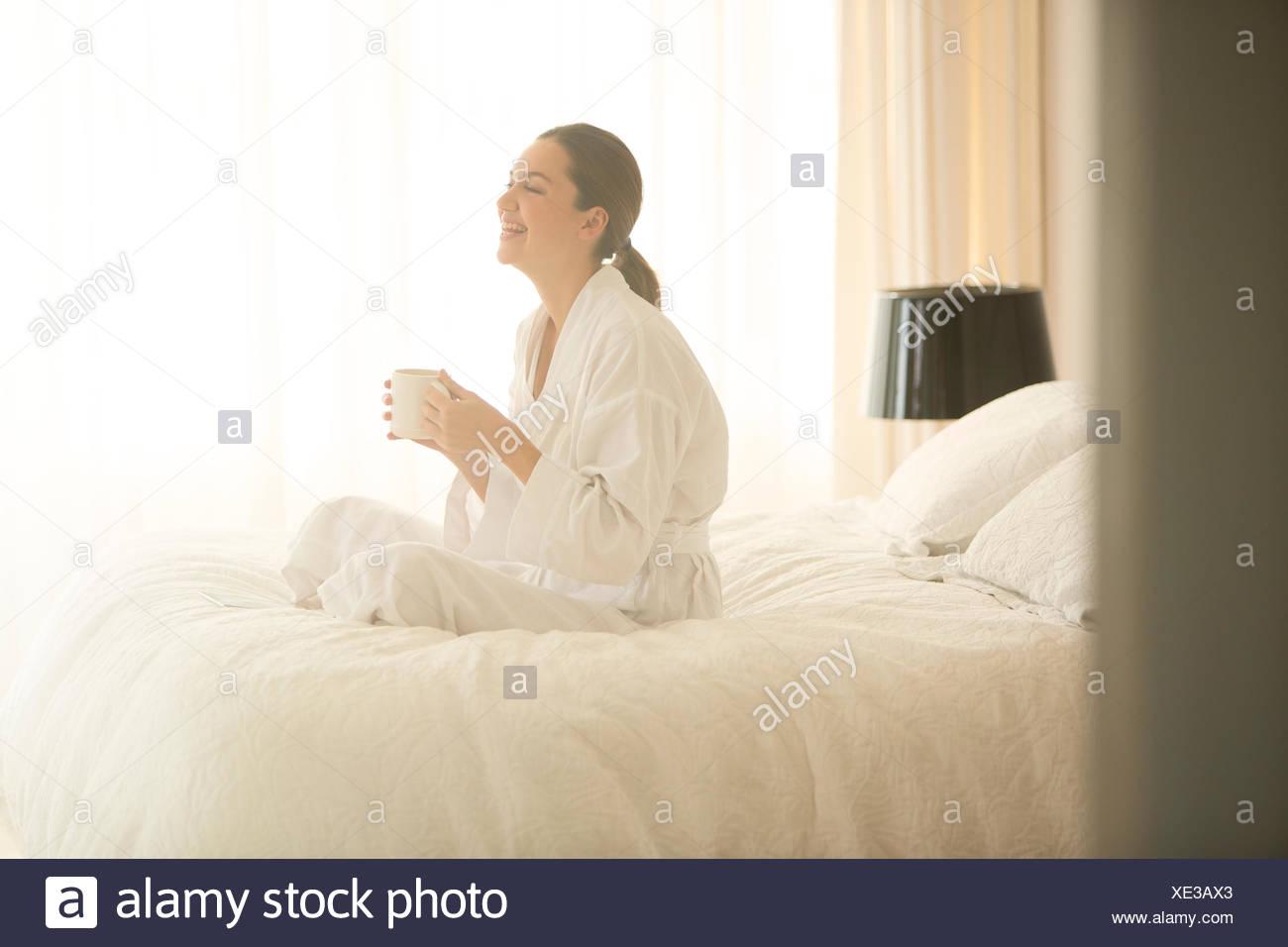 Smiling woman in bathrobe drinking coffee cross-legged on bed - Stock Image