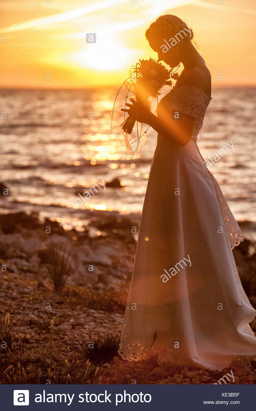 Bride smelling bouquet against sunset - Stock Image