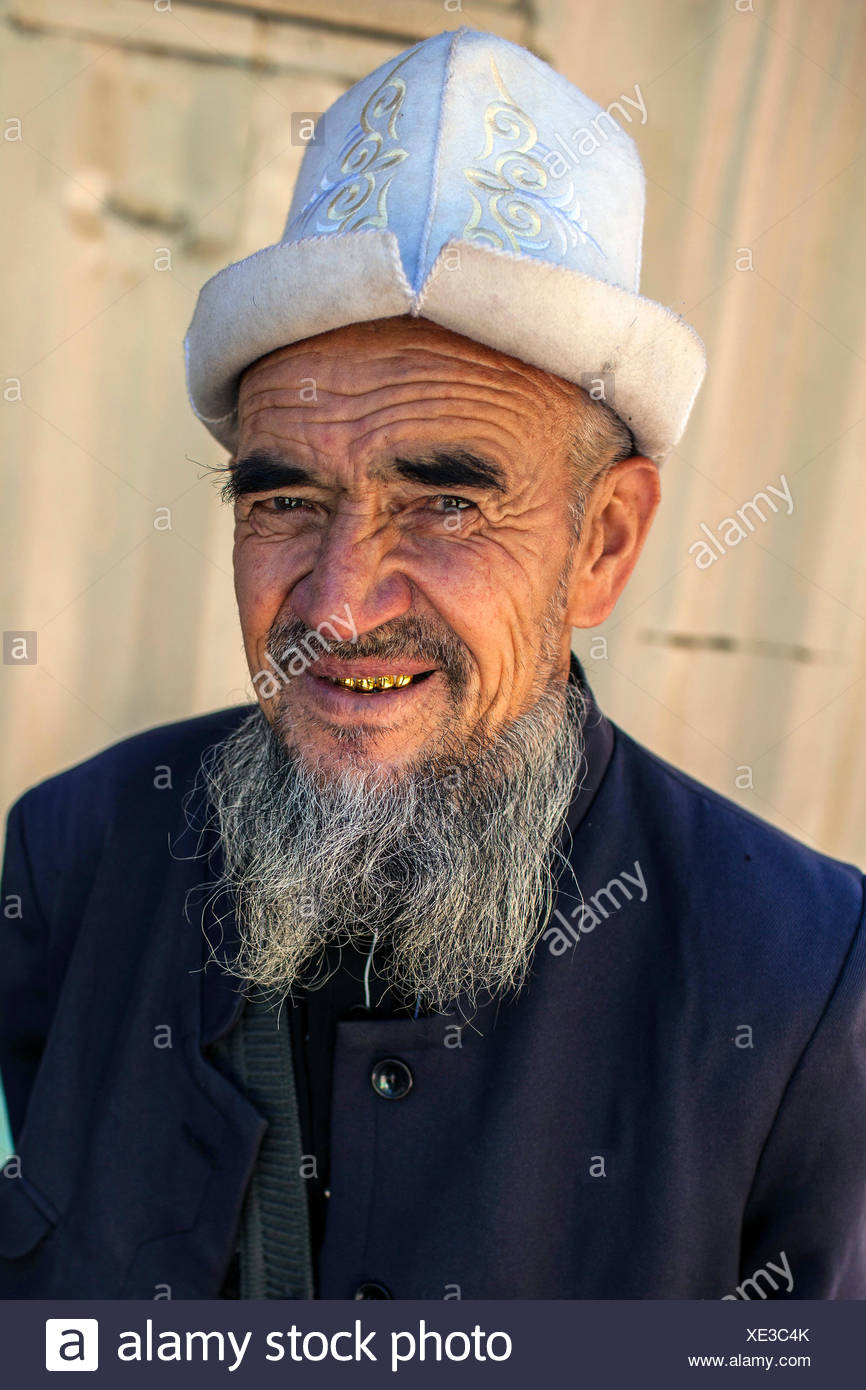 old Kirghizian man with typical gold teeth and beard plus traditional headdress, Kyrgyzstan, Djalalabad, Arslanbob - Stock Image