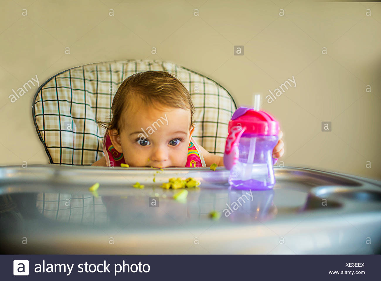 Portrait of shy baby girl in high chair - Stock Image