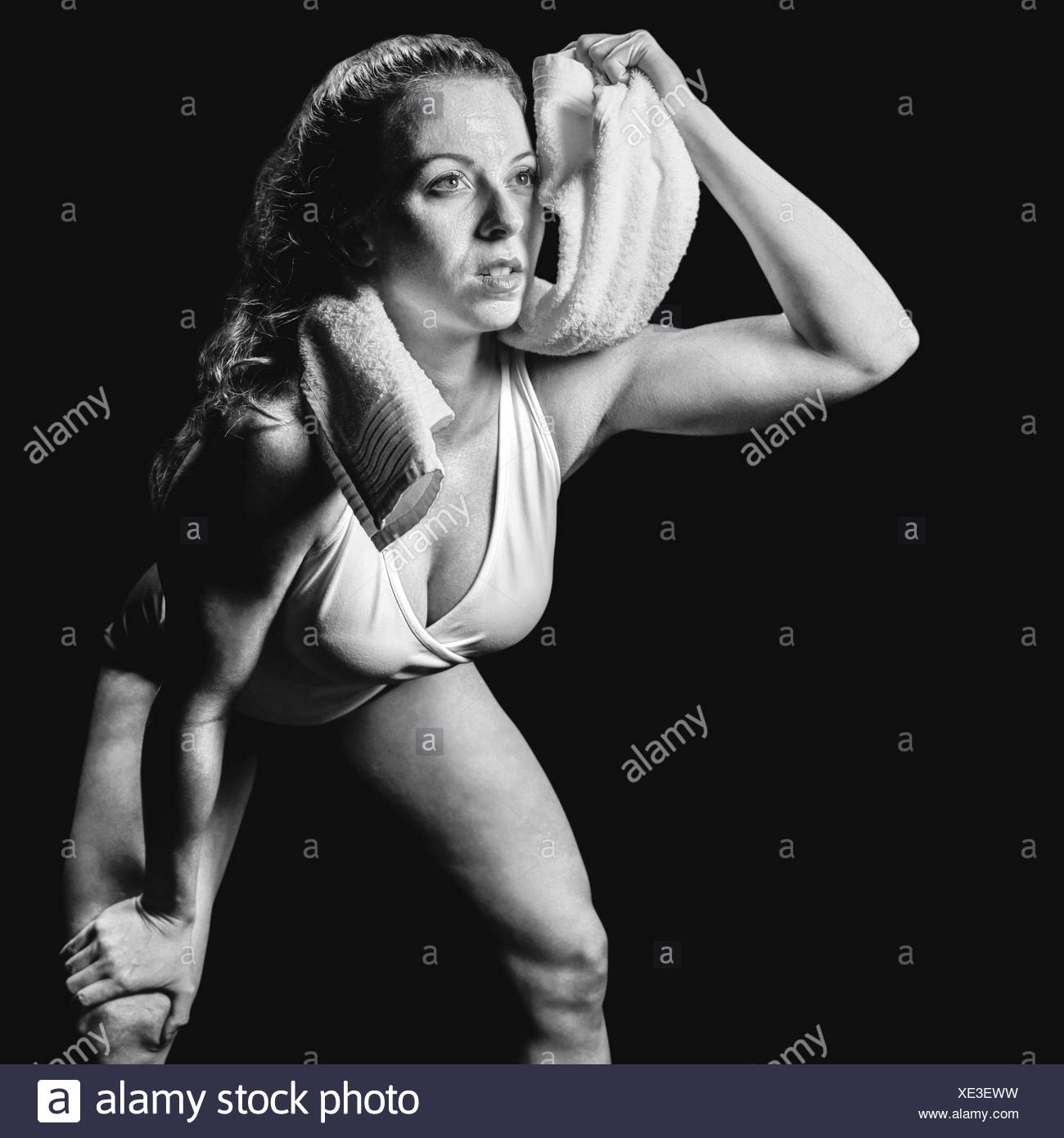 Composite image of athlete wiping sweat with towel while looking up - Stock Image