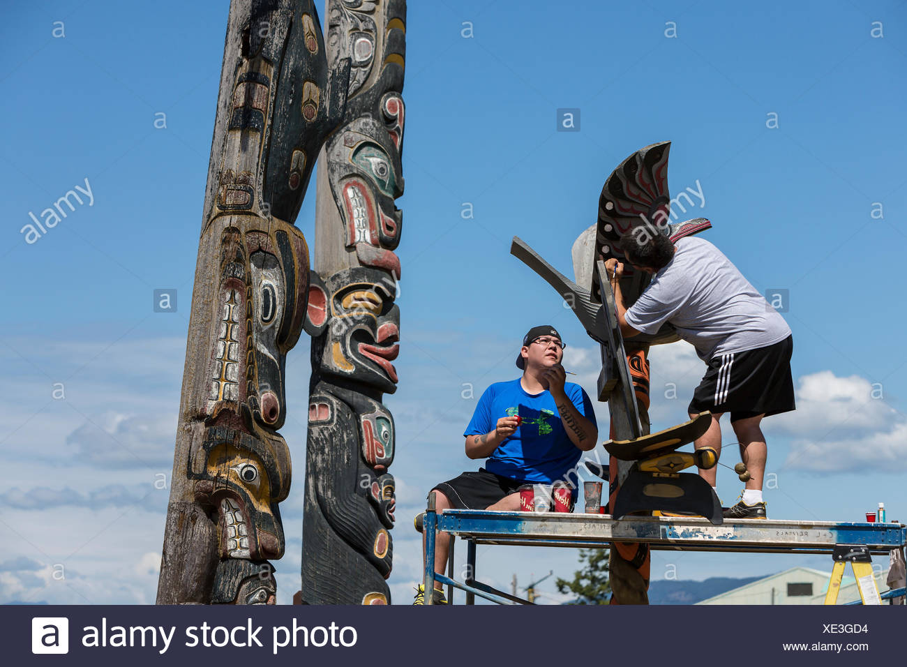 Two first nations family members refurbish a relatives memorial pole, Campbell River - Stock Image