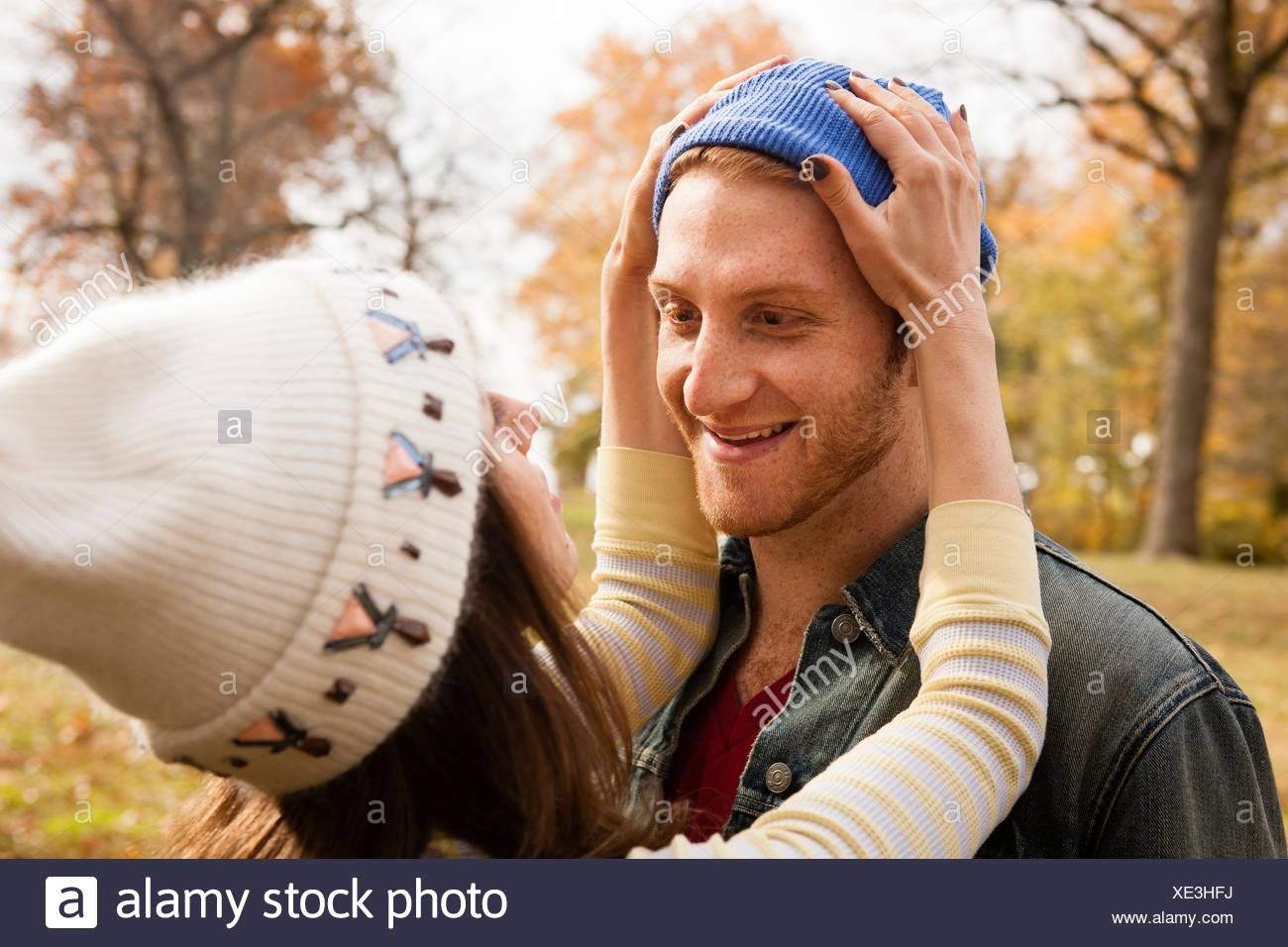Romantic young woman adjusting boyfriends knit hat in park - Stock Image