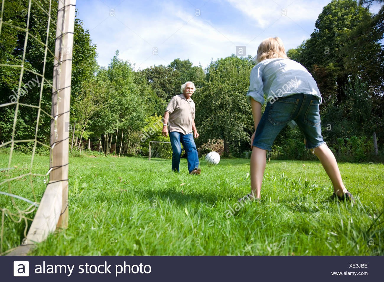 Grandfather tries to score a goal - Stock Image