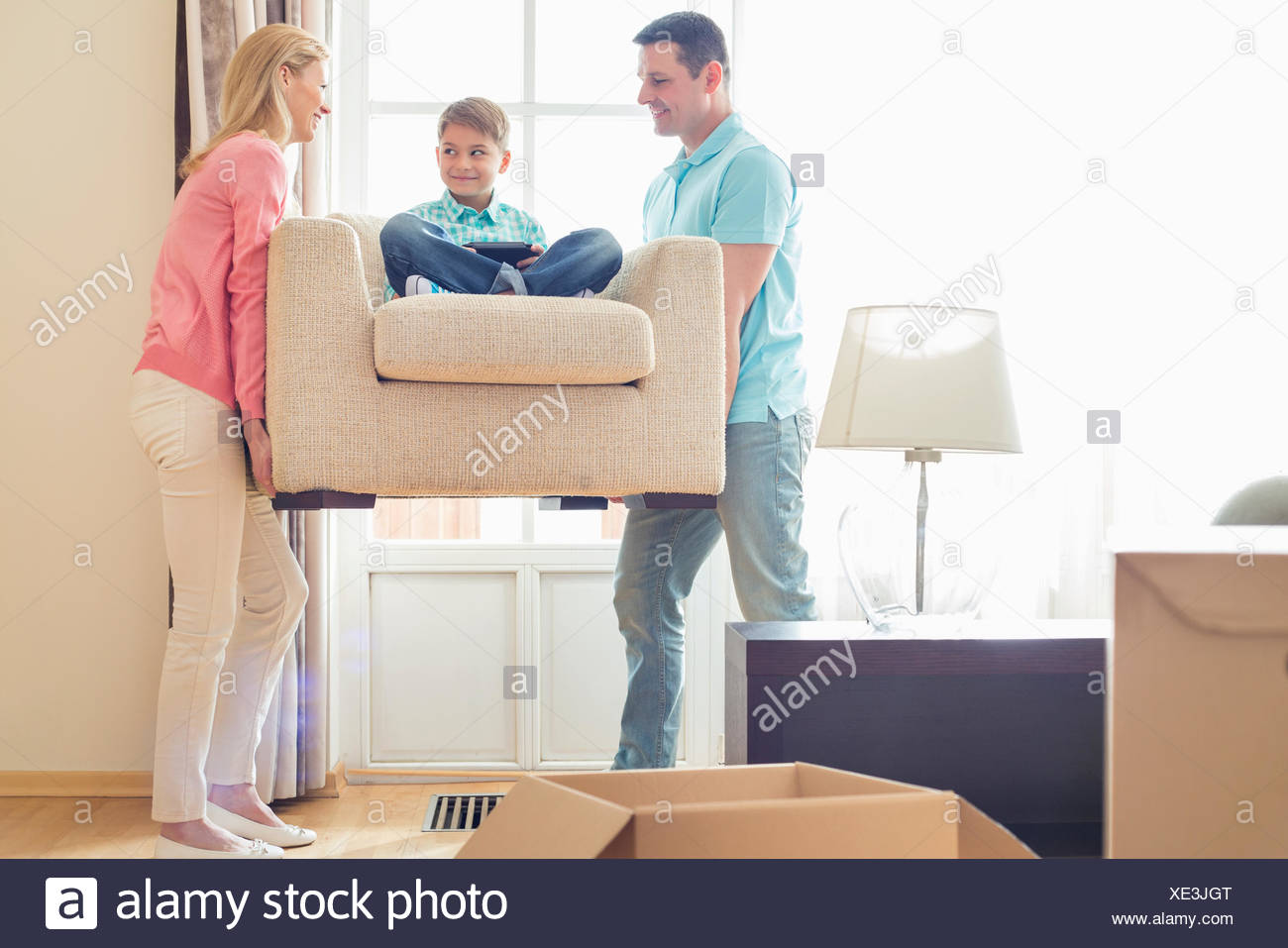 Parents carrying son on armchair in new house - Stock Image