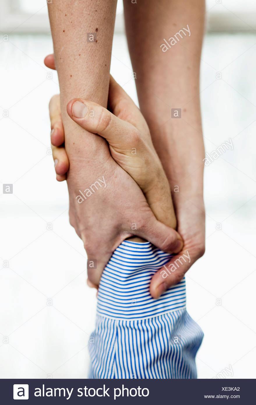 Woman grasping man's wrist, close-up - Stock Image