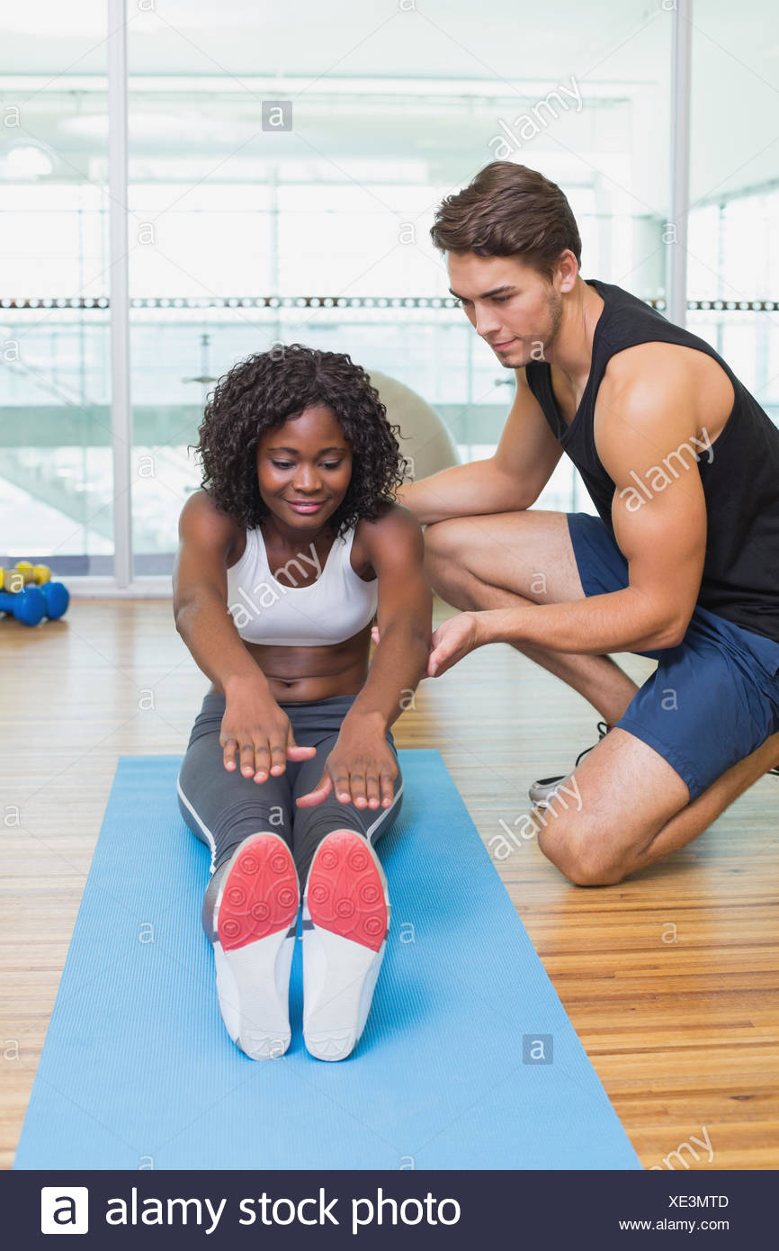 Personal trainer working with client on exercise mat Stock Photo