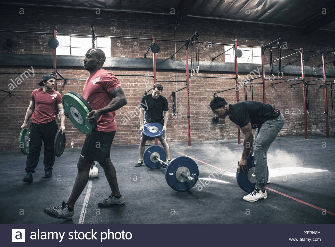 Men moving barbells in gym - Stock Image