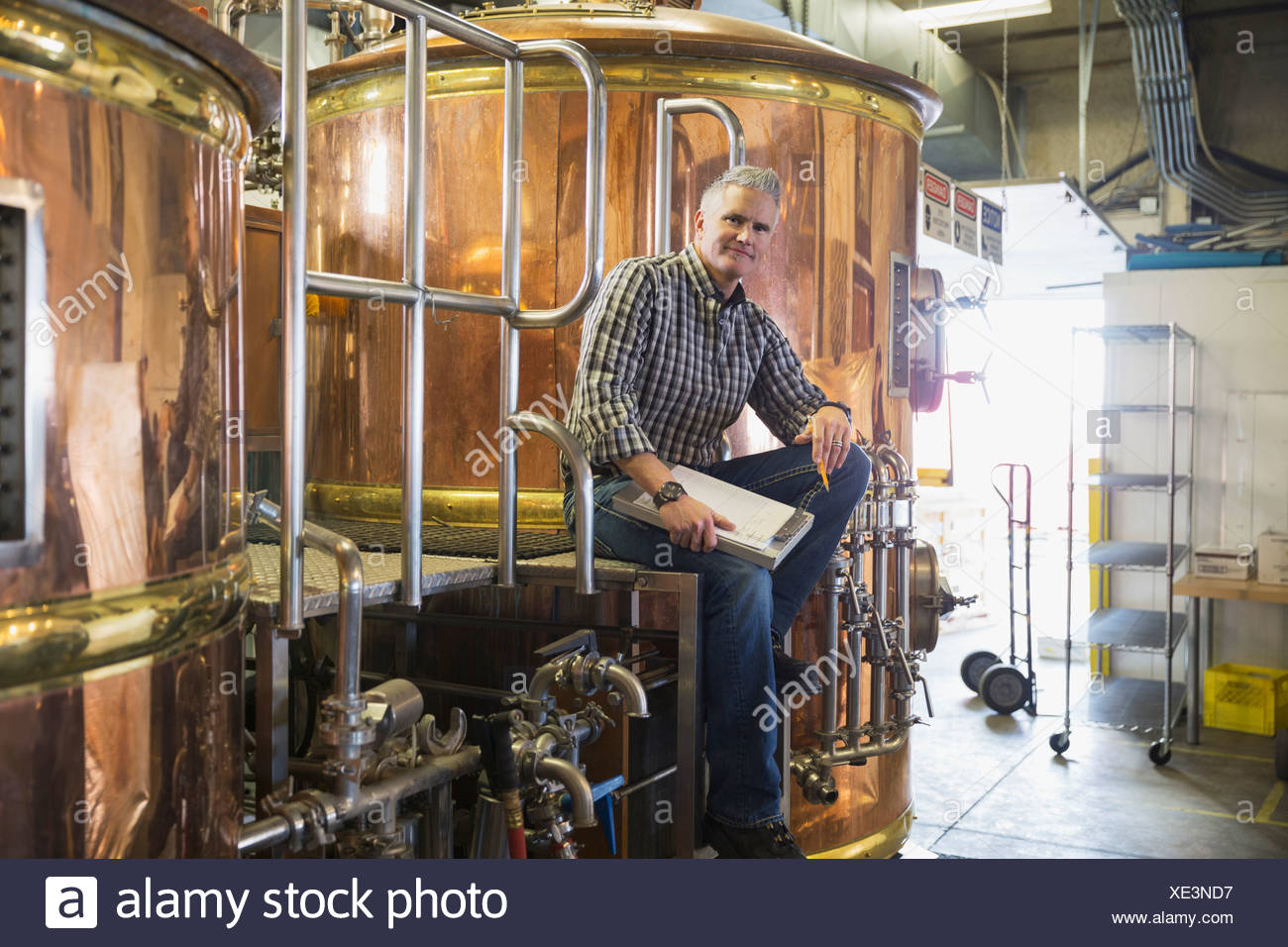 Portrait of brew master sitting at copper stills - Stock Image